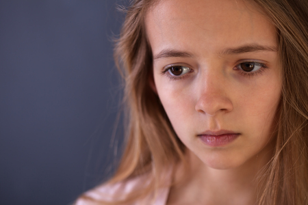 Young teenager portrait of a sad or worried girl on dark background - copy space