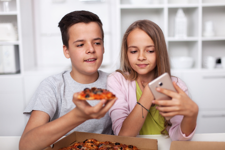 Young teenagers taking a selfie with their pizza in the kitchen - trying to catch a good angle Zdjęcie Seryjne