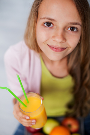 Young teenager girl with a glass of fresh fruit juice - close up portrait, looking up Zdjęcie Seryjne