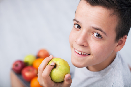 Young teenager boy holding an apple - looking up. Healthy eating concept, copy space Zdjęcie Seryjne