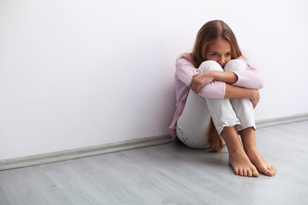 Young worried or sad girl sitting on the floor by the wall - knee hugging and looking away