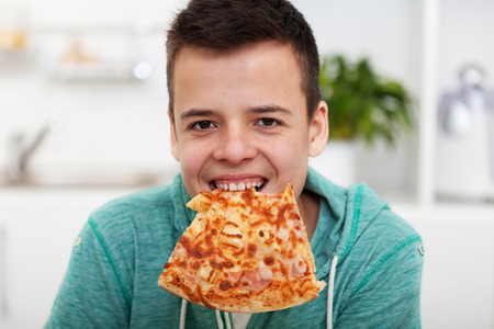 Young boy having fun eating a pizza in the kitchen at home - smiling with a slice hanging from his teeth