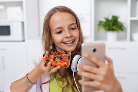 Happy teenager girl taking a selfie in the kitchen posing with a slice of pizza - the importance of online presence for youth