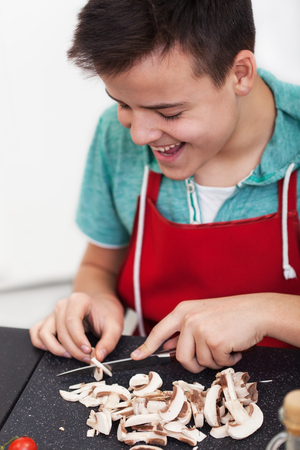 Young happy teenager boy preparing a dish in the kitchen - slice mushrooms on cutting board with a large smile, close up Zdjęcie Seryjne