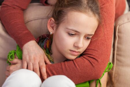 Mother holding sad teenager girl from behind trying to provide comfort and support in a dire situation - close up Standard-Bild