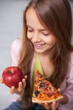 Fast food snack or fruits snack - smiling girl pondering eating both, holding a slice of pizza and an apple, close up portrait Foto de archivo