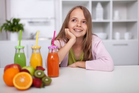 Young teenager girl sitting in the kitchen with bottles of colorful freshly squeezed fruit juices - healthy life concept