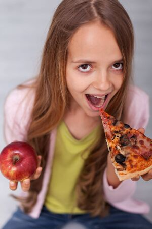 Giving in to temptation - young girl choosing the slice of delicious pizza instead of the healthy apple