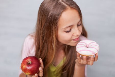 Young girl pondering healthy snacks versus sweets - the diet choices we make concept Stock Photo
