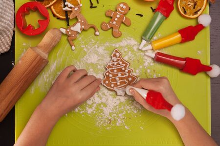 Child hands decorate christmas gingerbread cookies with white icing and pearls - top view Foto de archivo