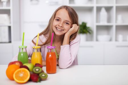 Happy teenage girl smiling, sitting in the kitchen with a variety of healthy fresh fruit juices - wholesome life with colorful diet choices, copy space