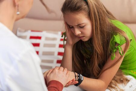 Counseling and support professional trying to provide comfort to sad teenager girl holding her hands in a hard situation - close up