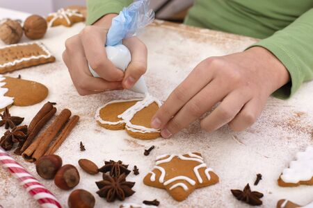 Young hands decorate gingerbread cookies with white icing - close up on table with ingredients Foto de archivo
