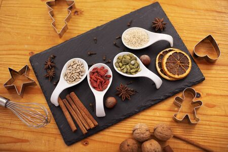 Various assorted seeds, dried berries and spices for the holiday cookies on the table with cooking utensils - christmas sweets ingredients and decorations, top view