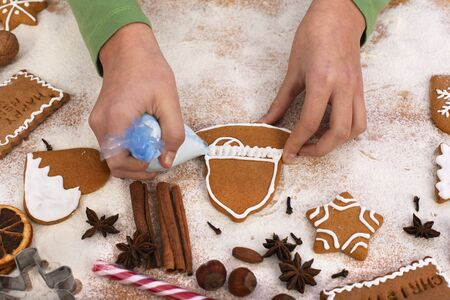 Young girl hands decorate gingerbread cookies with white icing holiday season food - close up, top view