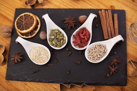 Various assorted seeds, dried berries and spices for the holiday cookies - christmas sweets ingredients and decorations Foto de archivo