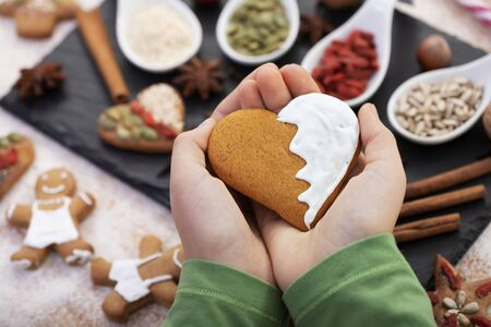 Hands holding gingerbread heart with white frosting over table filled with holidays specific sweets and ingredients - love christmas food concept Foto de archivo