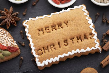 Christmas food concept - gingerbread cookie with merry christmas text baked on surface, close up