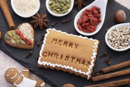 Merry christmas text baked in gingerbread biscuit with white icing among other holiday season sweets and ingredients