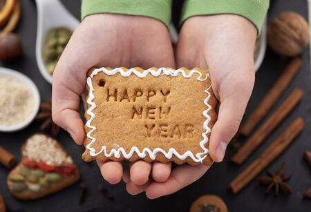 Young girl hands hold gingerbread biscuit with happy new year text and white icing - holiday season food Foto de archivo