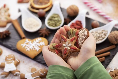 Hands holding gingerbread cookies decorated with natural seeds and dried berries - holiday sweets over christmas food setting Foto de archivo