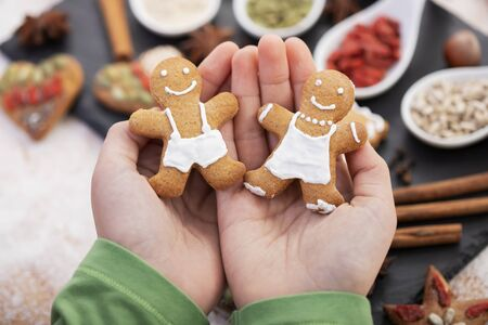 Young hands holding couple of gingerbread cookie people  - christmas sweets and holiday specific food in background