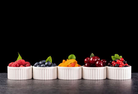 Fresh summer fruits in small recipients - with copy space. Colorful healthy snacks. Raspberry, blueberry, apricot slices, sour cherry and blackcurrant mixed with red currant berries