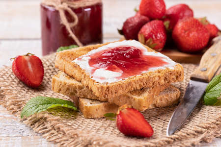 Delicious strawberry jam on toast bread - summer fruit preserve. Homemade sweets.