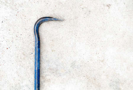 Metal crowbar lie in the left on the gray grunge concrete background