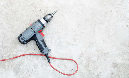 Electric drill with a red cord lies on a gray grunge concrete background Stock fotó