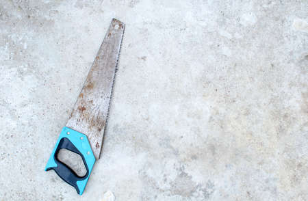 Old rusty hand saw with a blue handle lies on a gray grunge concrete background Stock fotó