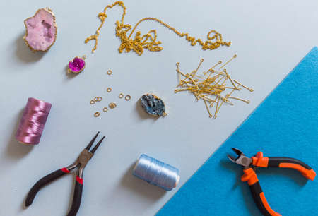 Jewelry making and beading process. Findings, pendants, geode and pliers. Making handmade jewelry. Accessories for needlework. Handmade accessories. Top view. Selective focus.