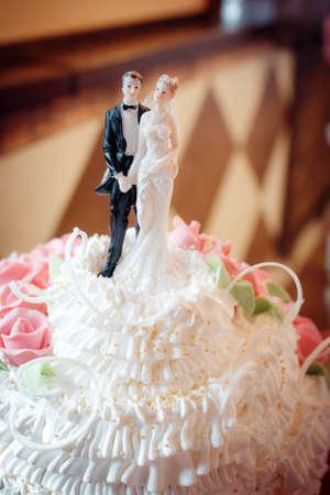 Classic figurines on a wedding cake the newlyweds, white Stock Photo