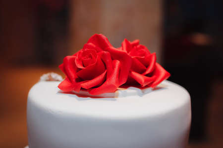 Gorgeous white cake decorated with red flowers roses ribbons gorgeous white cake decorated with red flowers roses ribbons and bow wedding stock mightylinksfo