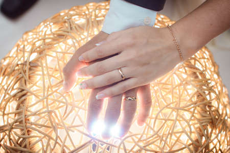 arms couple with rings lit by bright light, gold wedding Stock Photo