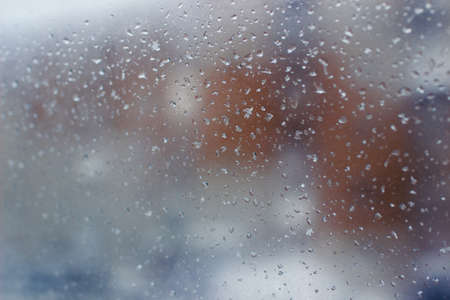 city landscape is hardly distinguishable through a muddy window with rain drops, orange structure