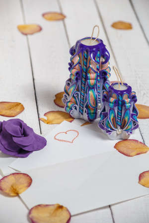 St. Valentines Day: two violet carved candles, flower and petals of roses. Symbol.