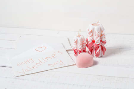 St. Valentines Day: the offer on a romantic appointment. Two carved candles, pink box and note. Love. Stock Photo