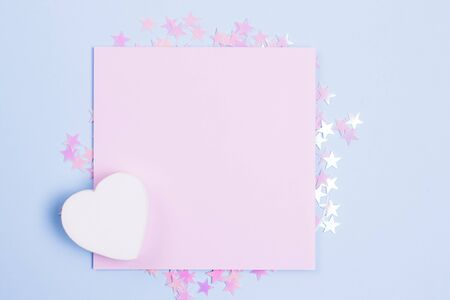 Pastel pink blank card mockup and white wooden heart on pastel blue background with scattered pink glitter stars. Place for your text. Gbar style.