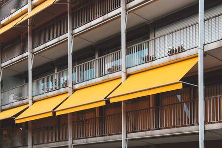 Schöner Balkon mit gelber Markise im Mehrfamilienhaus.
