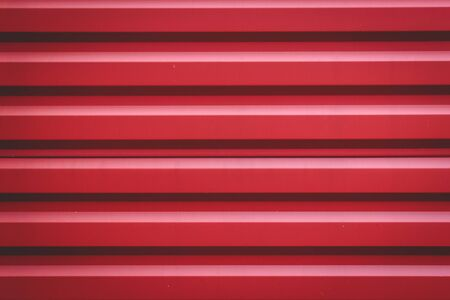 Red corrugated metal panel texture. Place for your design. Roofing material and building finishing.