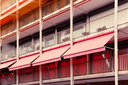 Balcony with coral awning in apartment house. Colorful image. Archivio Fotografico