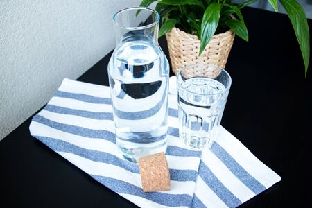 A glass and bottle of water, green plant in a pot on the table with a blurred background. Top view. Banco de Imagens - 128280616