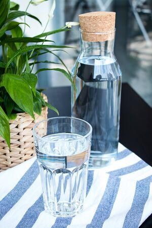 A glass and bottle of water, green plant in a pot on the table. Beautiful fresh background. Summer hugge. Banco de Imagens - 128280618