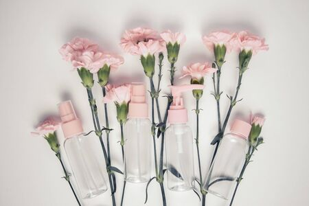 Glitch effect. Nice carnation flowers and group of small bottles for travelling on a light background. Flat lay composition of cosmetic products. Zerowaste.