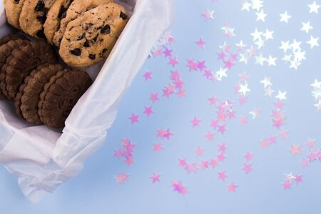 Homemade tasty cookies in a white box on a pastel blue background with pink stars confetti.