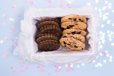 Tasty cookies in a box on a pastel blue background with pink stars confetti.