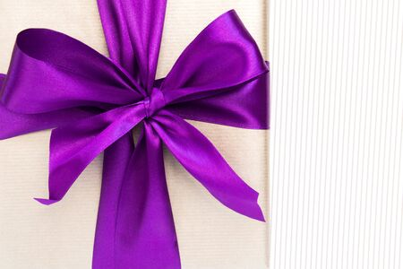 Vertical gift with violet ribbon and bow-knot on light background. Copy space.