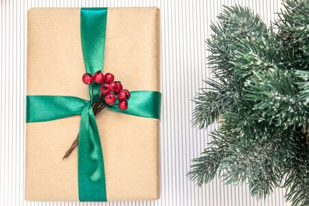 Gift in craft paper with green ribbon, red berries, branches of spruce on a white background. Banco de Imagens