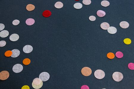 Color confetti on a dark background. Background for holiday.